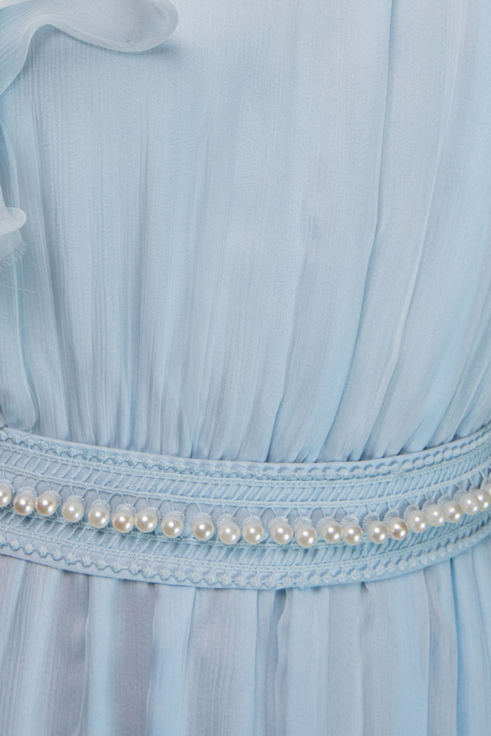 One-shouldered ice-blue gown with ruffled collar and ripple sleeve, pearl studded waistband